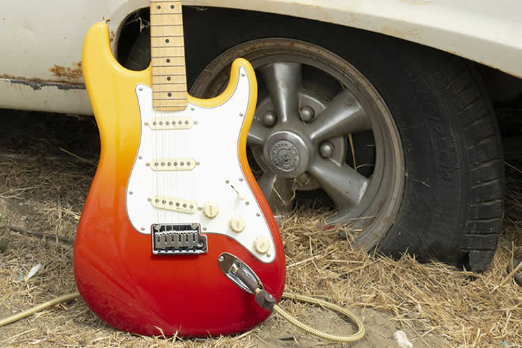 Player Plus Stratocaster leaning against old car