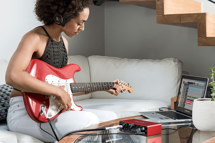 Image of person recording guitar.