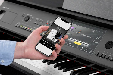 Image of hand holding a phone in front of a Clavinova digital piano