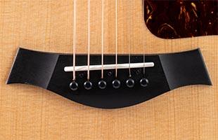 detail image of Taylor 214ce-K DLX showing bridge saddle