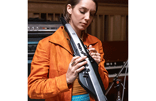 musician playing Roland Aerophone Pro AE-30 in project studio