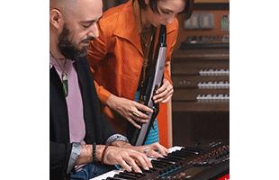 musician playing Roland Aerophone Pro AE-30 in recording studio alongside keyboardist playing Roland Fantom workstation keyboard