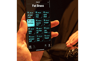 point-of-view image of musician playing Roland Aerophone Pro AE-30 while holding smartphone running Roland companion app