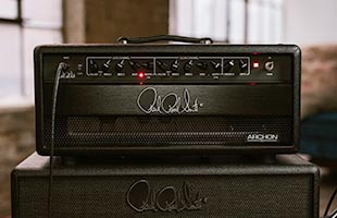 front view of PRS Archon 50 Head sitting atop PRS amplifier cabinet in warehouse rehearsal space