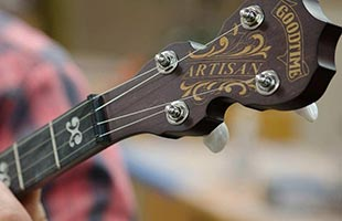 detail image of Deering Artisan Goodtime Two showing fiddle-shaped peghead with engraved Goodtime logo