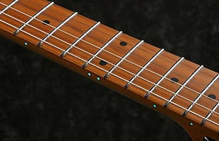 detail side image of Ibanez AZ2204B neck in dark environment showing luminescent side dot inlays
