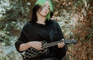 Billie Eilish in forest setting playing Fender Billie Eilish Signature Ukulele