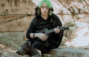 Billie Eilish sitting on bench in forest setting playing Fender Billie Eilish Signature Ukulele