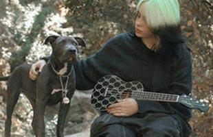 Billie Eilish sitting down in forest setting petting dog while holding Fender Billie Eilish Signature Ukulele