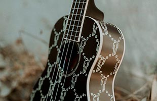 close-up perspective view of Fender Billie Eilish Signature Ukulele in forest setting showing top, right side and part of neck