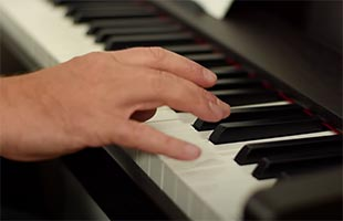 detail image of musician's hand playing keys on Korg C1 Air