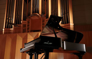 Kawai grand piano in concert hall with pipe organ in background