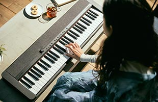 over-the-shoulder view of musician playing Casio Casiotone CT-S1 - Black on living room table