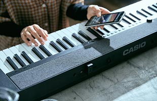 close-up view from front of musician playing Casio Casiotone CT-S1 - Black while holding Bluetooth-connected mobile phone