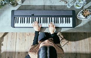 view from above of musician playing Casio Casiotone CT-S1 - Black on dining room table
