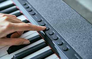 detail image of musician's finger pressing Tone selection button on Casio Casiotone CT-S1 - Black control panel
