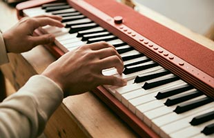 close-up side view of musician playing Casio Casiotone CT-S1 - Red on living room table