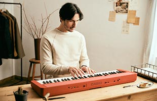 front view of musician playing Casio Casiotone CT-S1 - Red on desk