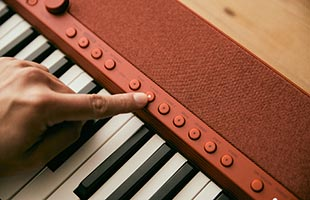 detail image of musician's finger pressing Tone selection button on Casio Casiotone CT-S1 - Red control panel