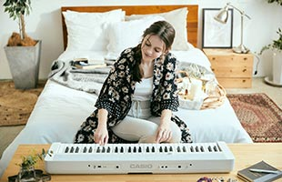 front view of musician playing Casio Casiotone CT-S1 - White on bedside table