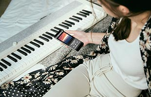 over-the-shoulder image of musician playing Casio Casiotone CT-S1 - White while holding Bluetooth-connected mobile phone