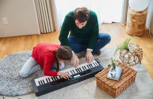 father and daughter playing Casio Casiotone CT-S400 on living room floor
