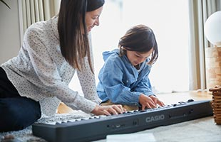 mother and daughter playing Casio Casiotone CT-S400 on living room floor