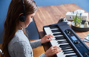 side view of musician playing Casio CT-S400 on dining room table while wearing headphones