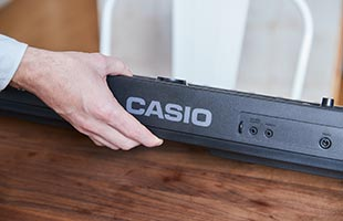 close-up view of musician's hand lifting Casio Casiotone CT-S400 to install batteries