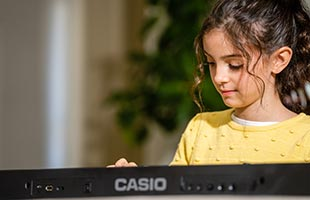 front view of musician playing Casio Casiotone LK-S450 at dining room table