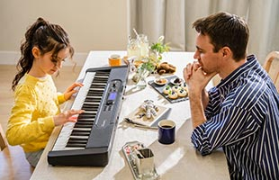 father and daughter sitting across from one another at dining room table while daughter learn piano using Key Lighting learning system on Casio Casiotone LK-S450