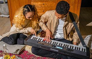 couple playing Casio Casiotone LK-S450 on living room floor while one wears it on an attached strap