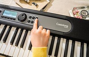 close-up image of musician's finger pressing sound selection button on Casio Casiotone LK-S450 control panel