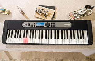 top view of Casio Casiotone LK-S450 on dining room table with some keys up internally via Key Lighting learning system