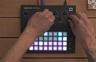 close-up top view of musician's hands manipulating controls on Novation Circuit Tracks