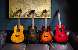 four Yamaha CSF1M acoustic guitars sitting on sofa in natural, transparent black, tobacco brown sunburst and crimson red burst finishes