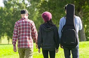 three people walking away from camera with one wearing Yamaha CSF1M acoustic guitar gig bag using backpack straps