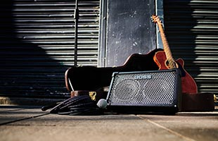 front view of Boss Cube Street II sitting on sidewalk with guitar case and guitar in background