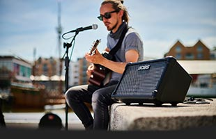 side view of seated musician performing outdoors with guitar, microphone and Boss Cube Street II