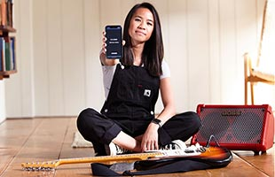 front view of musician seated in studio holding up smartphone running Boss Cube Street II Editor app surrounded by guitar and Boss Cube Street II