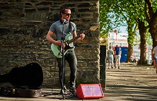 front view of standing musician performing outdoors with guitar, microphone and Boss Cube Street II