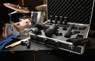 PreSonus DM-7 microphone kit in included case with lid open on top of road case with drum set in background
