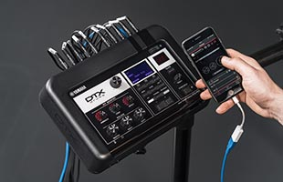 Yamaha DTX-PRO drum module on stand with hand holding smartphone running companion practice app