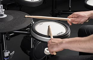 close-up image of drummer's hands holding drumsticks playing Yamaha DTX6 series drum kit with XP80 snare