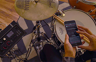 drummer's hands holding smartphone running Yamaha EAD10 companion app with drum set and EAD10 module in background