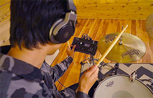 rear closeup view of drummer wearing headphones and interacting with Yamaha EAD10 module with drum kit in background