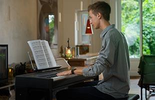 musician in home living room setting playing Kawai ES520 digital piano