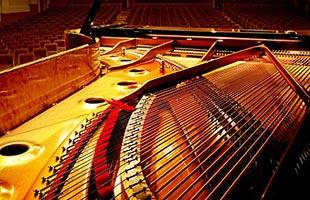 dramatic close-up image of strings inside Kawai grand piano