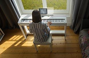 musician in home living room setting playing Kawai ES920 digital piano