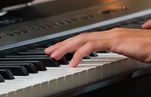 close-up image of hands playing Kawai ES920 digital piano